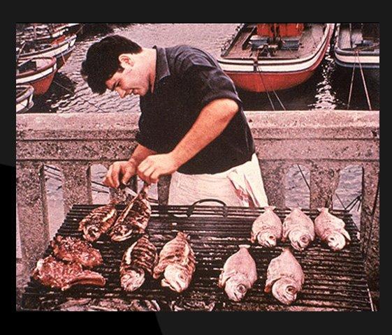 Balık ızgara yapan bir adam Dünyamızı tanıtan her türlü fotoğraf bulunmakta.