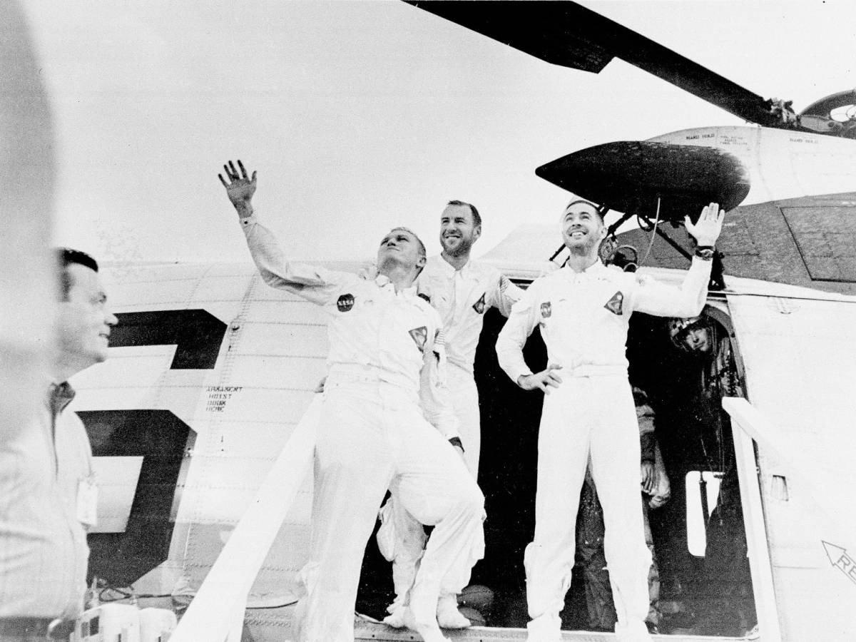 Apollo 8 astronotları Frank Borman, William Anders ve James Lovell, başarılı bir ay yörüngesi operasyonundan sonra dünyaya dönmüş, kurtarma helikopterinden inerken onları karşılayanları selamlıyor.